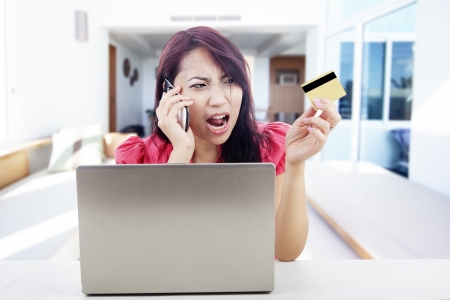 Angry woman talking on the phone with laptop and holding credit card, shot at home photo