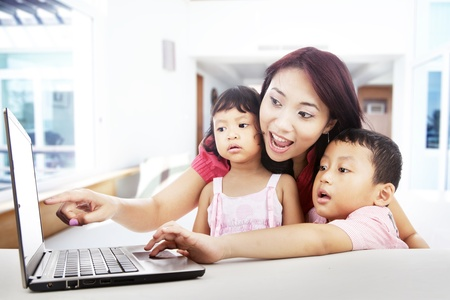 Happy mother pointing on the screen of laptop with her children surfing on internet photo