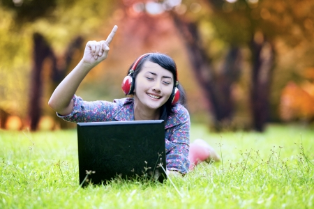 adult indonesia: Beautiful asian woman enjoying music in the park. shot during autumn