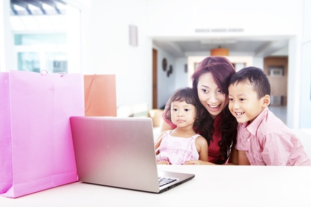 Happy asian family shopping online by using laptop computer, shot at home photo