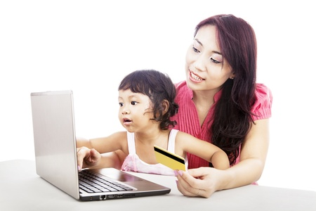 Young asian woman gives online shopping education to her daughter by using laptop and credit card photo