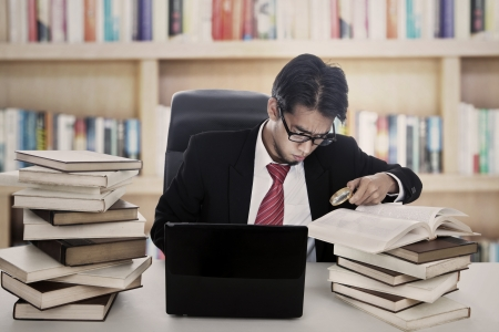 Businessman finding information from textbooks using magnifying glass. shot in library photo