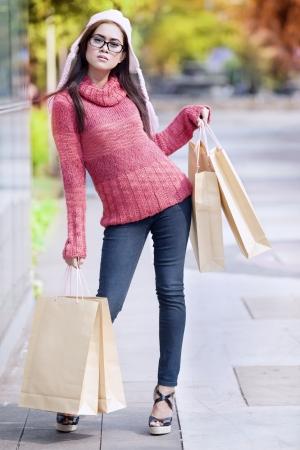 sueteres: Retrato de niña glamour llevar bolsa de la compra y se vistió para el invierno con el sombrero en la cabeza.