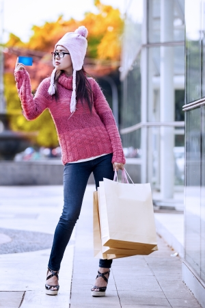 Portrait of young girl carrying shopping bag and holding credit card. photo