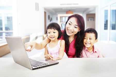 Happy young mother with her children using ultrabook laptop computer to enjoy entertainment at home photo