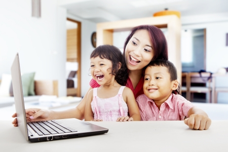 Happy young mother with her children using ultrabook laptop computer in their house photo