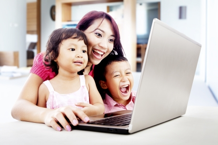 japanese children: Happy young mother with her children using ultrabook laptop computer in their house