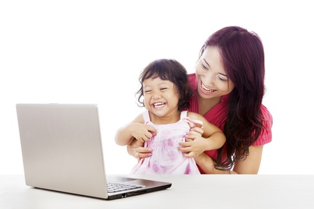 surfing the internet: Shot of happy young mother and daughter with ultrabook laptop computer isolated on white