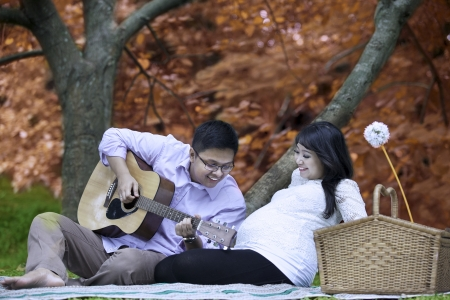 Portrait of happy father playing guitar for his unborn baby on autumn day photo