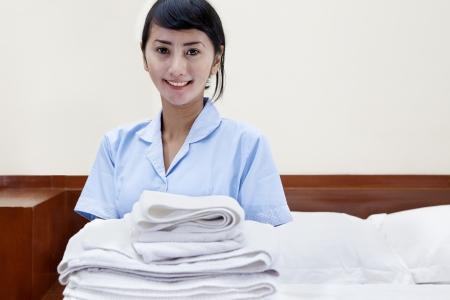 sirvienta: Señora sonriente joven con toallas de limpieza en una habitación de hotel