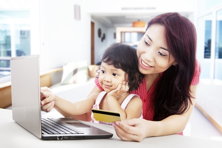 card payment: Young asian woman gives online shopping education to her daughter, shot at home