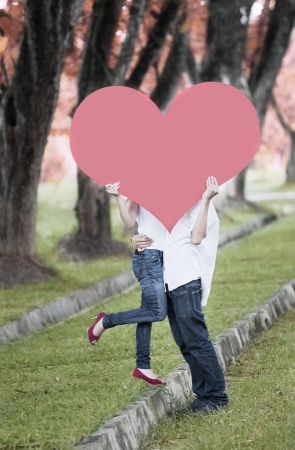 Young couple kissing behind red heart cutout in the nature on the autumn day photo