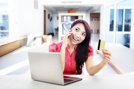 llamando: Una atractiva mujer de compras en línea de productos utilizando su ordenador portátil, tarjeta de crédito y teléfono móvil, un disparo en su casa