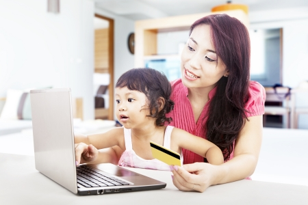 buying a house: Young asian woman online shopping using credit card with her daughter, shot at home Stock Photo