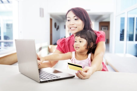 Young asian woman online shopping using credit card with her daughter, shot at home photo
