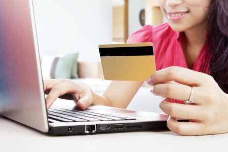 Smiling woman online shopping with laptop and a credit card, shot at home Stock Photo - 15474273