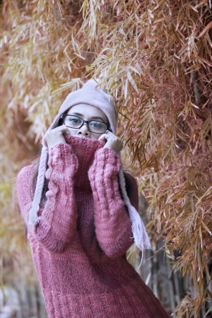 Portrait of playful woman with winter sweater on autumn day photo