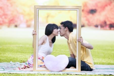 parejas jovenes: Par asi�tico bes�ndose en el parque con marco rectangular y de color rosa en forma de coraz�n de San Valent�n. un disparo durante el oto�o