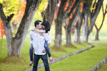 date tree: Portrait of romantic young couple with handsome boy carry pickaback his girlfriend in autumn day