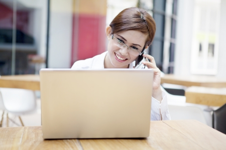 ultrabook: Portrait of beautiful secretary using cellphone with laptop in the office