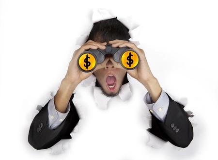 breaking through: Hombre de negocios dado una sacudida el�ctrica de �ltima hora a trav�s de una pared de papel mirando a trav�s de binoculares con signo de d�lar en la lente