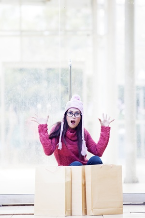 Portrait of shocked girl with shopping bags and dressed for winter time  shot at mall photo