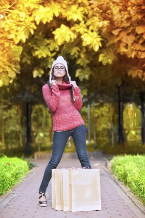 Portrait of young girl with shopping bag posing in autumn park  shot outdoor during autumn photo