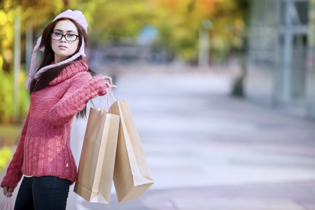 Portrait of young girl carrying shopping bag and dressed for winter time with hat on her head Stock Photo - 15474315