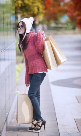 Happy young girl carrying shopping bag and dressed for winter time with hat on her head  photo