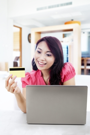 costumer: Satisfied woman shopping online with laptop and a credit card at home
