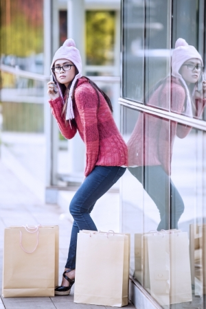 Portrait of shopping woman with bags calling to someone using mobile phone  shot outdoor photo