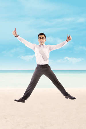 Successful asian businessman showing thumbs-up at beach photo