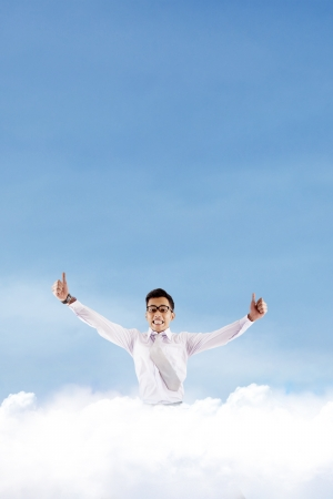 Successful asian businessman showing thumbs-up on the cloud photo