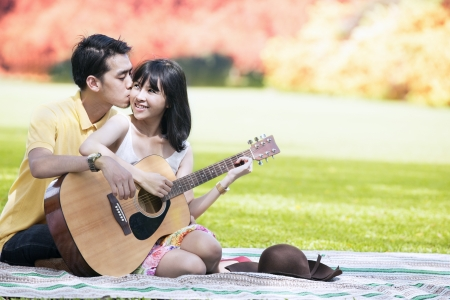 Romantic young couple playing guitar in the park during autumn day