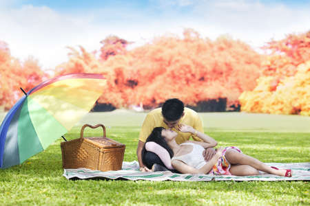 lying in leaves: Romantic young couple picnic together in the park  shot during autumn day