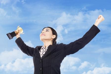 triunfador: Una mujer de negocios feliz celebrando su victoria con el trofeo en la mano Foto de archivo