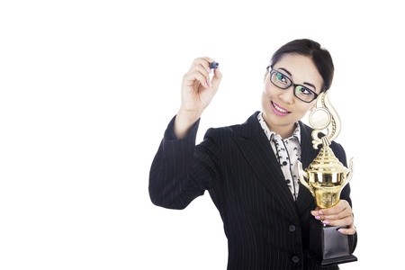 Businesswoman holding trophy while writing something on copyspace/board Stock Photo - 15637897
