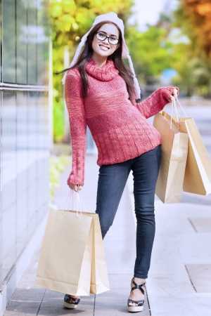 Portrait of friendly girl carrying shopping bag and dressed for winter time with hat on her head. Stock Photo - 15637891
