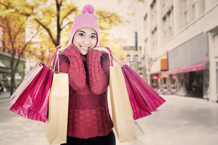 Portrait of woman wearing sweater and carrying shopping bags. shot during autumn day photo
