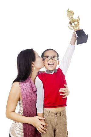 Orgullosa madre besar a su hijo con la celebración de un trofeo que gana. rodada en el estudio aislado en blanco Foto de archivo