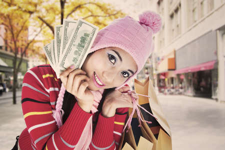 Portrait of fashionable woman holds money and shopping bag dressed for winter. shot on the street photo