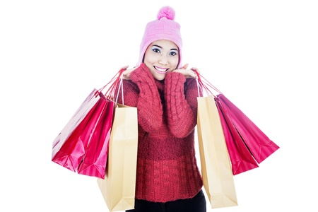 Portrait of young woman carrying shopping bags and dressed for winter. shot in studio isolated on white photo