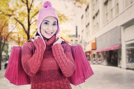 Portrait of woman wearing sweater and carrying shopping bags photo
