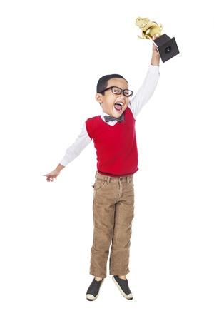 trophy winner: Mladý šťastný elementární student drží trofej a skok na oslavu svého úspěchu. izolovaných na bílém Reklamní fotografie