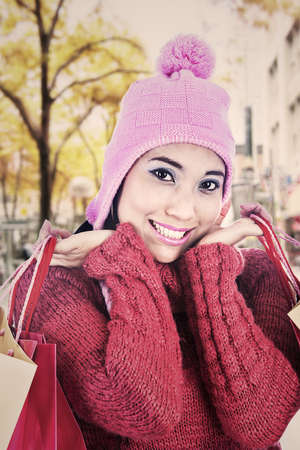 sweater girl: Portrait of smiling woman carrying shopping bags and dressed for winter. shot during autumn day Stock Photo