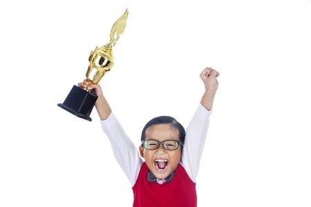 trophy cup: A young happy elementary student holding a trophy and celebrate his success. isolated on white Stock Photo