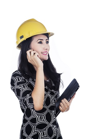 Female architect is talking with her college on the phone while holding tablet photo