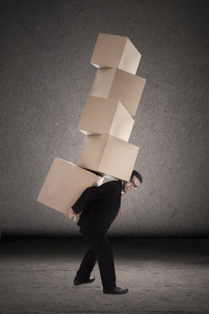 Businessman is trying to balance plenty of boxes that he is carrying photo