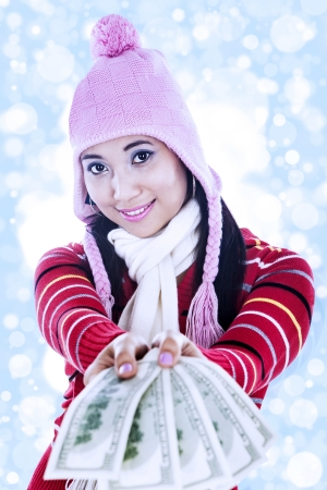 Beautiful young woman wearing winter clothes giving out one hundred dollar bills photo