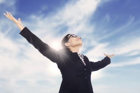 Businesswoman is stretching her arms under the blue sky photo